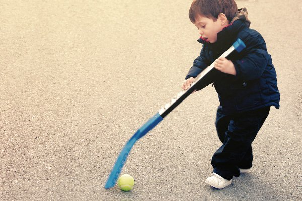 Little boy playing road hockey