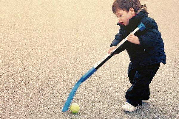 Little boy playing road hockey