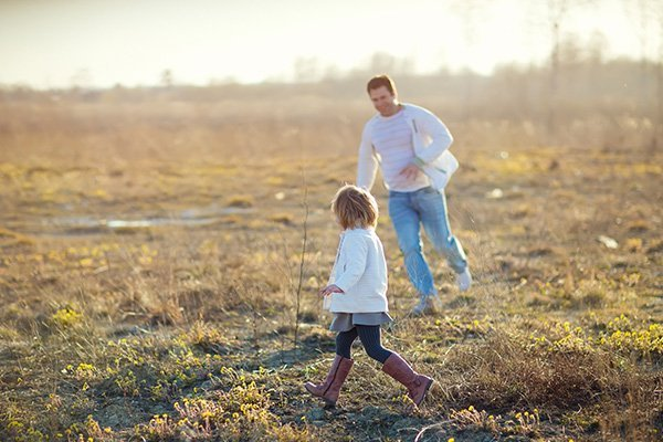 Father and daughter running on the grassy field
