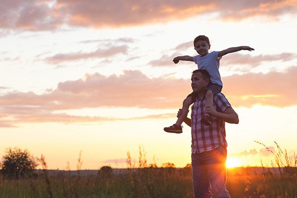 Father carrying his son on his shoulders with sunset behind them