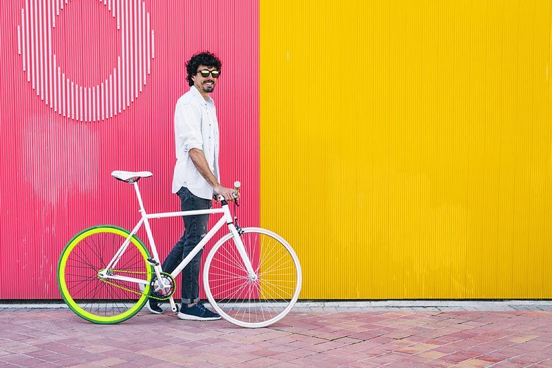 a man with his bike against a bright pink and yellow wall