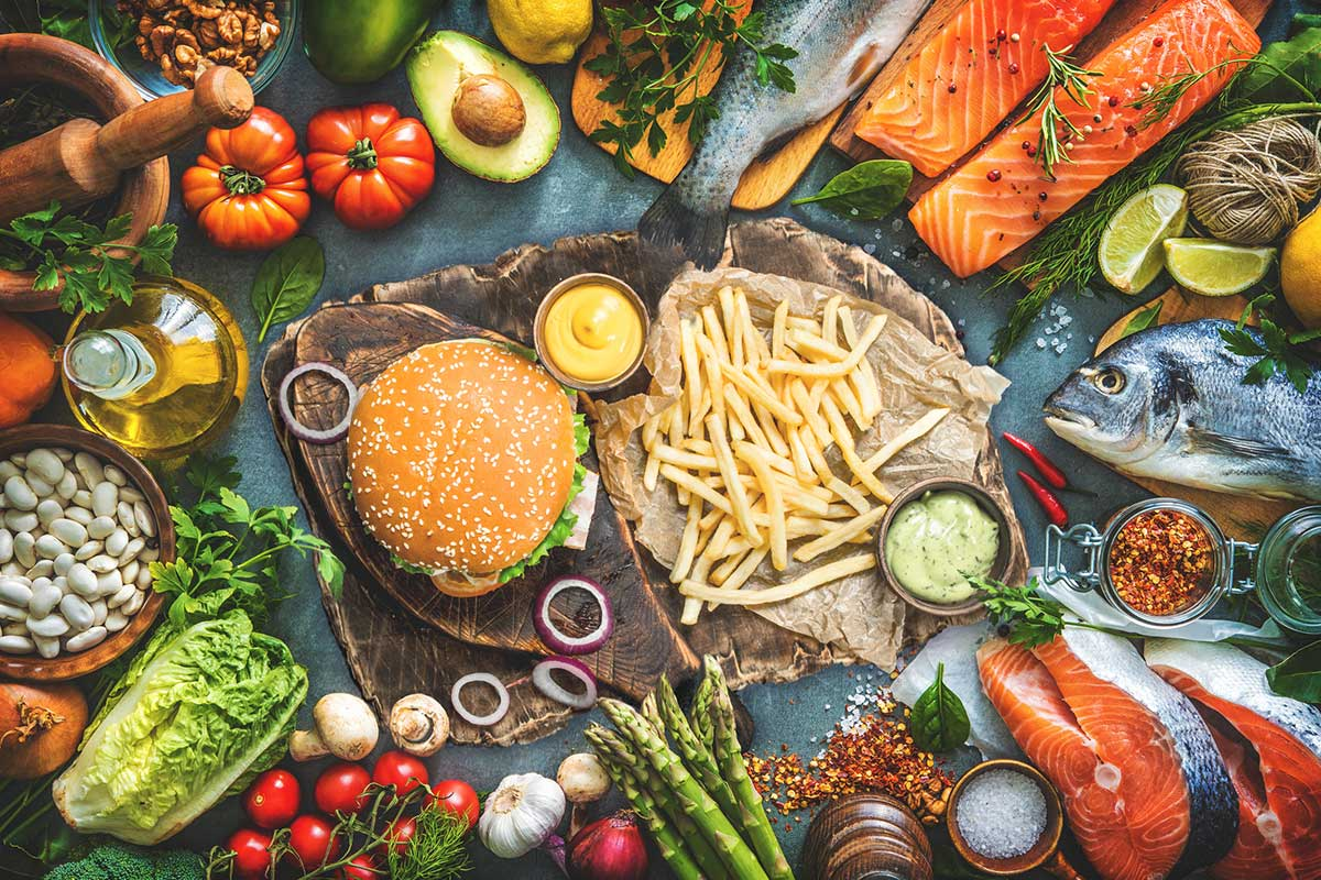 A burger and fries surrounded by a plethora of healthy food items
