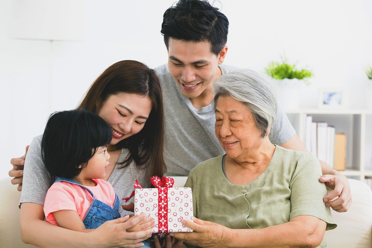 Asian family looking at gift box