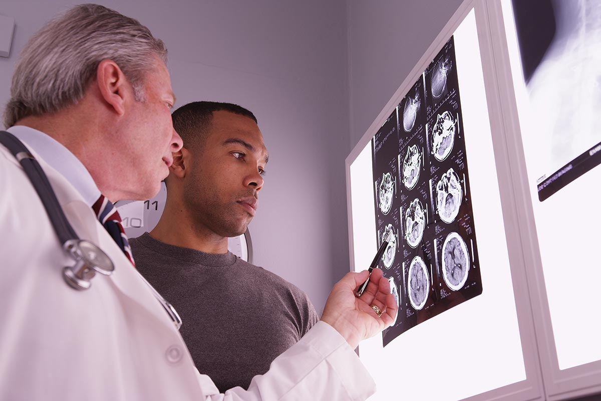 Doctor checking MRI scans for brain injury with patient