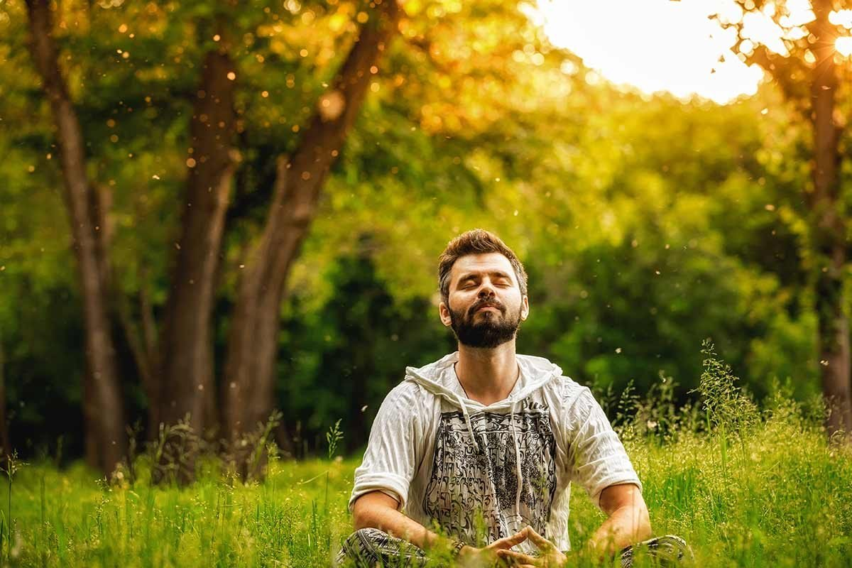Man meditating on a field of grass