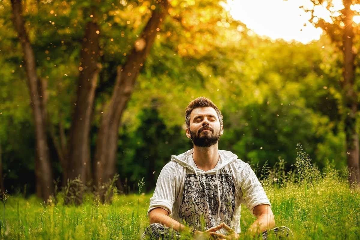 Man meditating on a field of grass