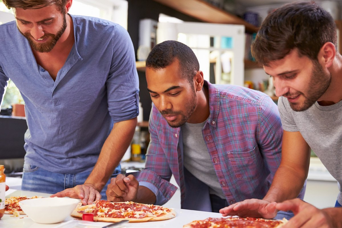 male friends eating pizza together