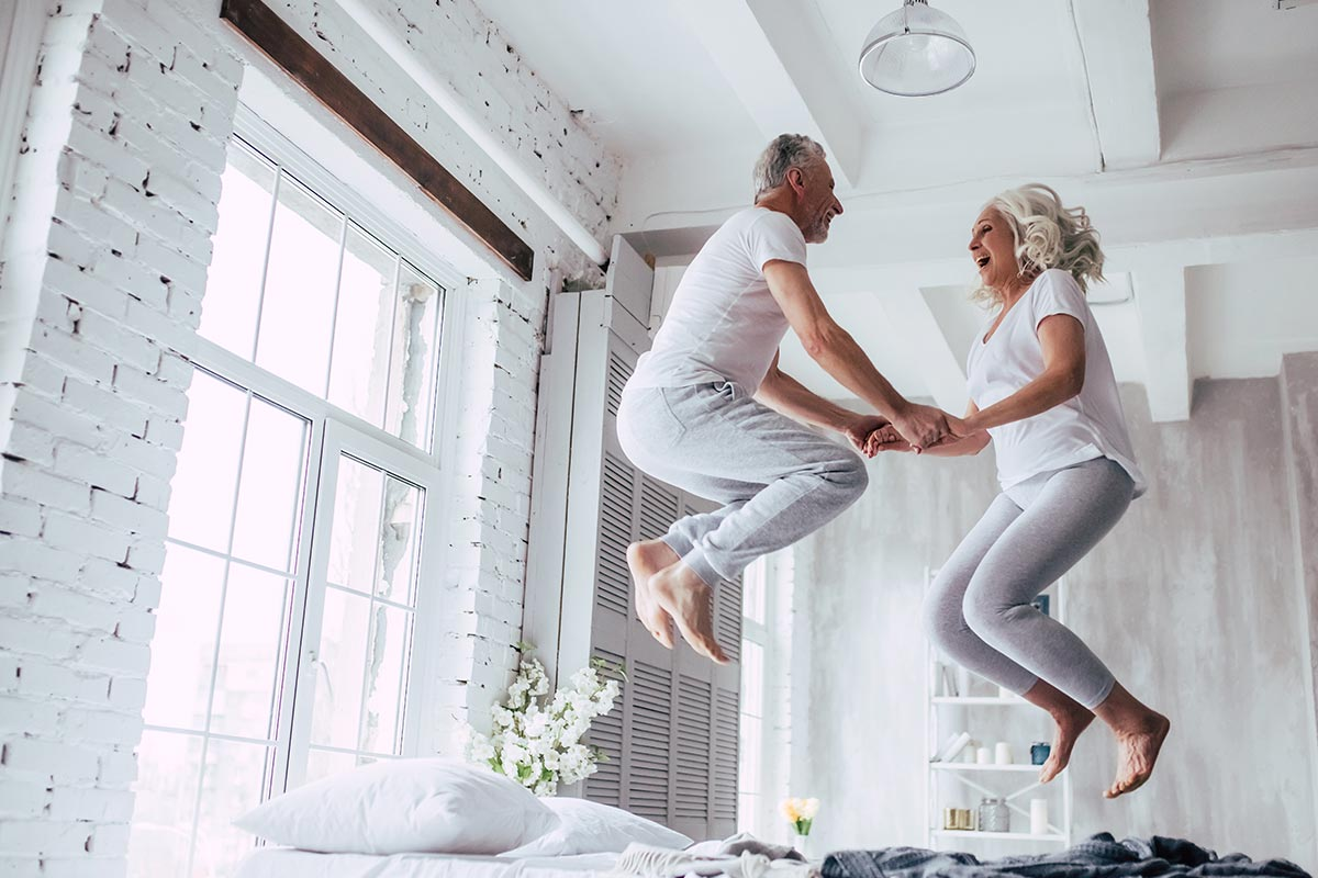 An elderly couple jumping on a bed