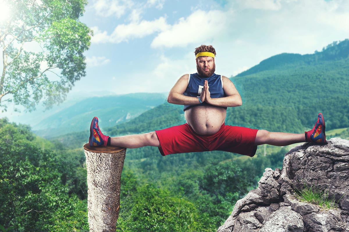 Overweight man balancing on a cliff