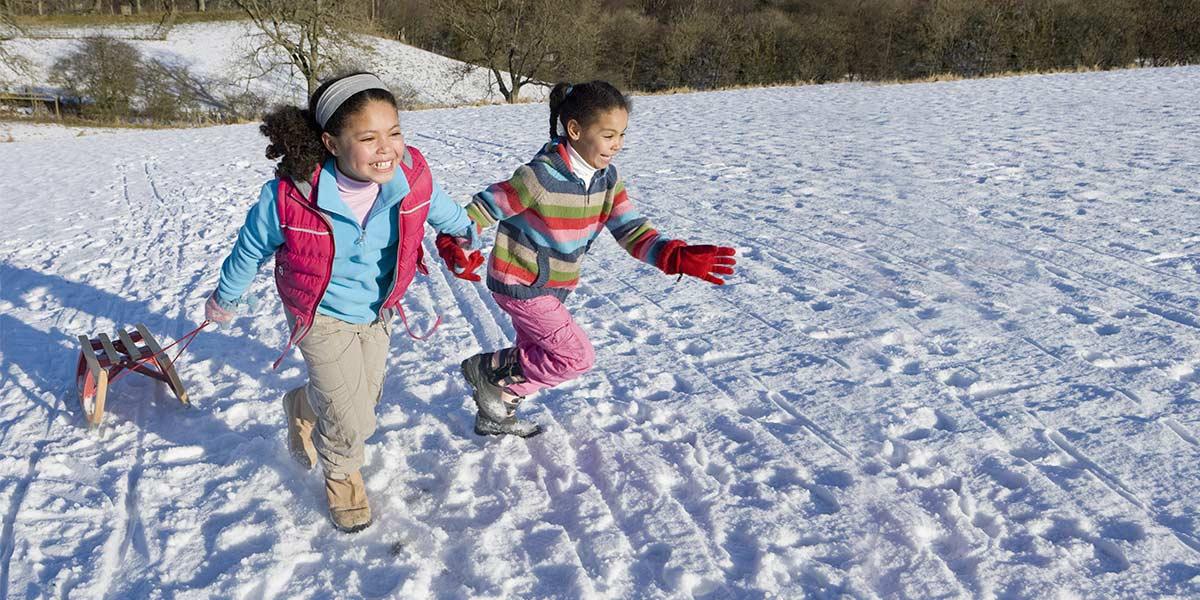 Two children running up a toboggan hill