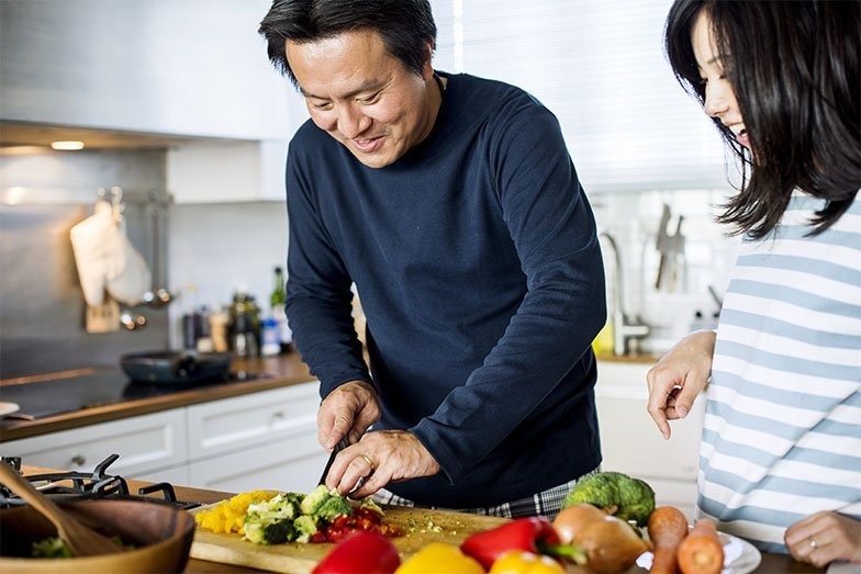 A man impressing his wife with his dicing skills in the kitchen.