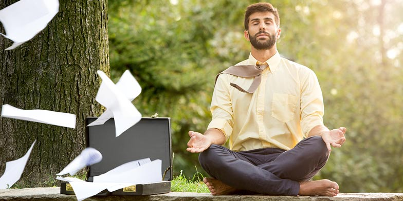 a businessman meditating in a green space