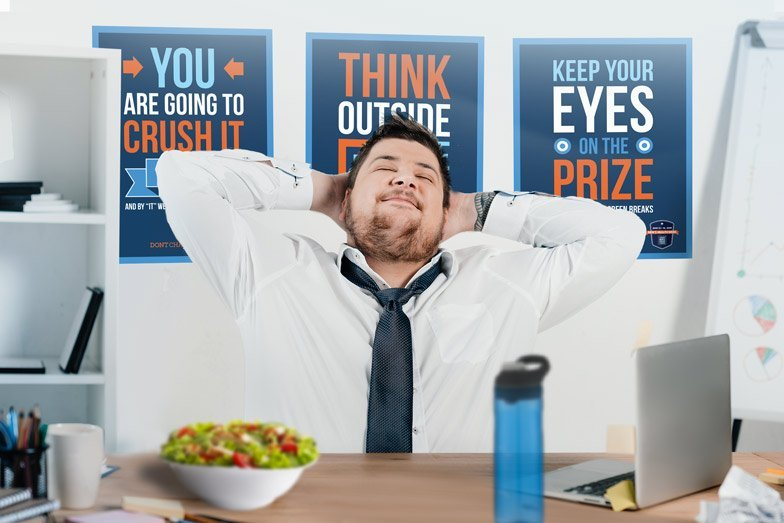 A man sitting happily at the office with three motivational posters behind him