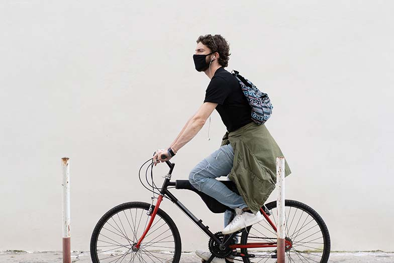 Young man riding his bike stress free and wearing a mask amid COVID-19 pandemic