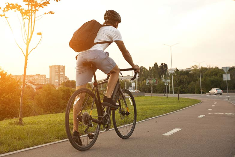 Young guy in casual clothes is cycling on the road in the evening city