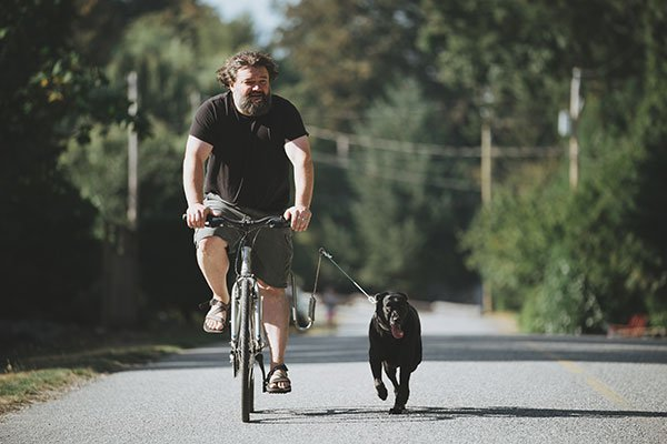 Toby Hargrave riding his bike and running the dog at the same time