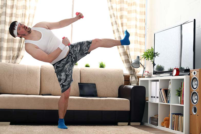 guy exercising in the living room at home upon social distancing due to coronavirus pandemic