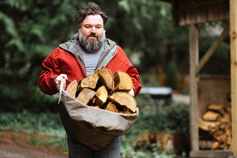 Toby Hargrave carrying firewood outdoors