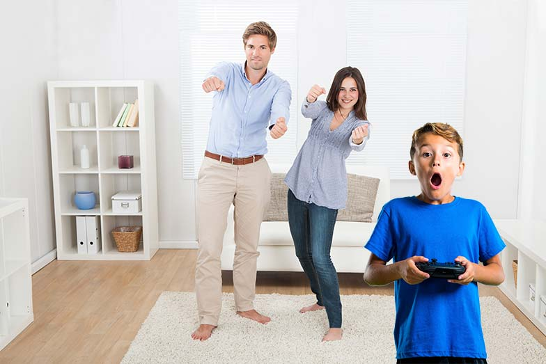 Dad, mon, and son playing an active video game in the living room