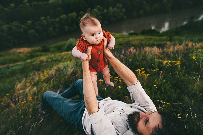 Dad lying on the grass lifting his baby