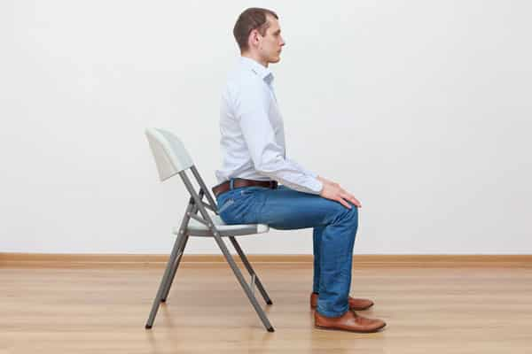 Man sitting upright in chair