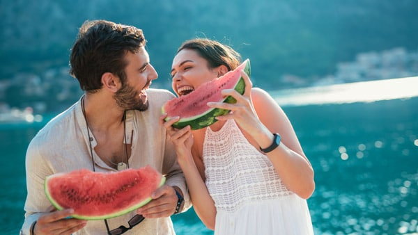 Two people eating watermelon for hydration