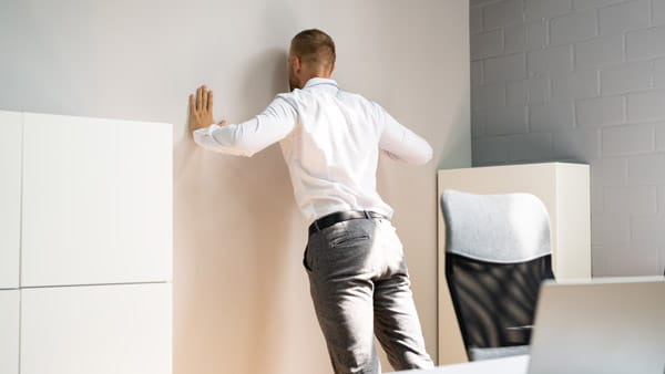 man doing wall push ups in office